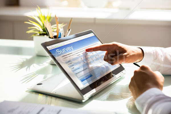 Businessman filling online survey form on laptop Stock photo © AndreyPopov