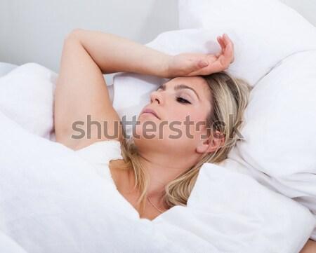 Upset woman lying on bed Stock photo © AndreyPopov