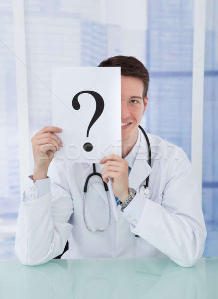 Stock photo: Doctor Holding Paper With Question Mark At Desk