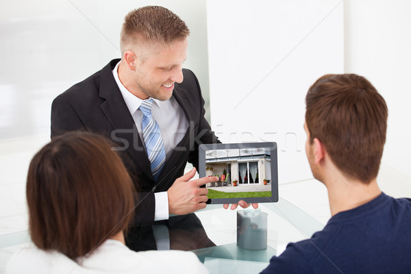 Advisor Showing House Picture To Couple On Tablet Stock photo © AndreyPopov