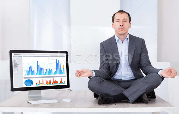 Businessman Mediating By Computer On Desk Stock photo © AndreyPopov