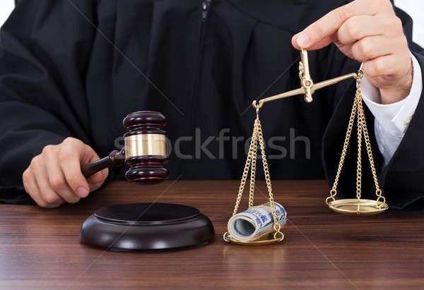 Judge Striking Gavel While Holding Scale With Money Stock photo © AndreyPopov