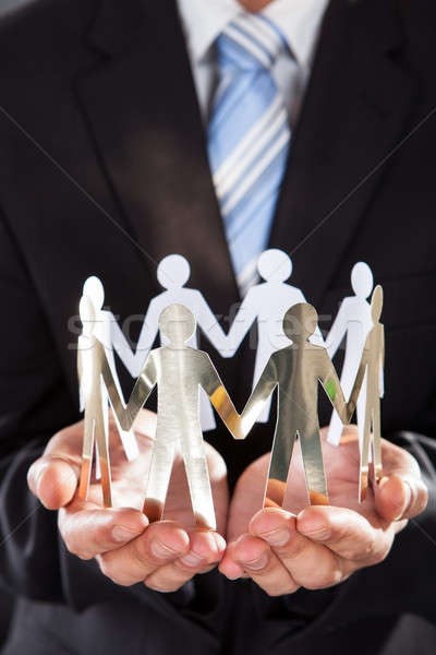 Businessman Holding Metal Team In Cupped Hands Stock photo © AndreyPopov