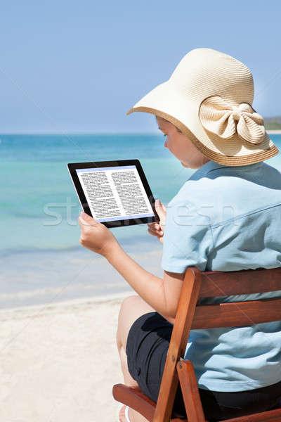 Kobieta czytania ebook plaży widok z tyłu posiedzenia Zdjęcia stock © AndreyPopov