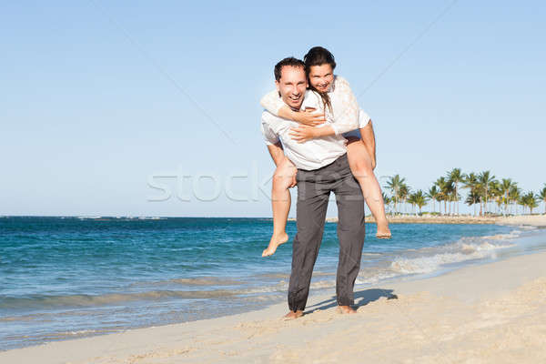 Man Giving Piggyback Ride To Woman At Beach Stock photo © AndreyPopov