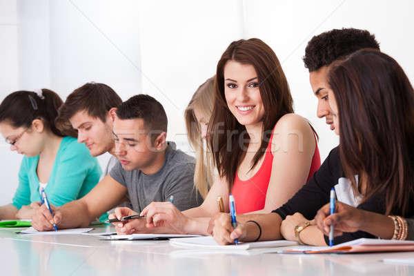Gyönyörű diák ül osztálytársak ír asztal Stock fotó © AndreyPopov