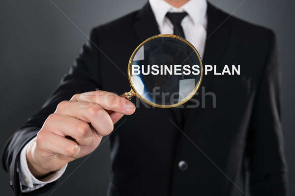 Businessman Showing Business Plan Through Magnifying Glass Stock photo © AndreyPopov