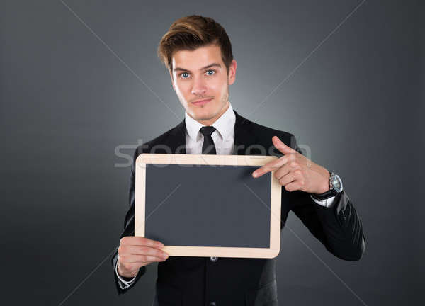 Confident Businessman Pointing At Blank Slate Stock photo © AndreyPopov