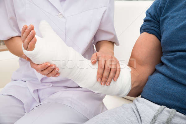 Female Doctor Holding Fractured Hand Of A Patient Stock photo © AndreyPopov