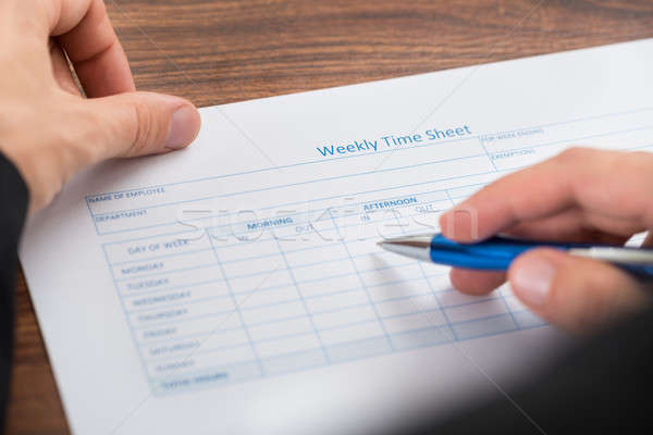 Person's Hand Filling Blank Weekly Time Sheet Stock photo © AndreyPopov