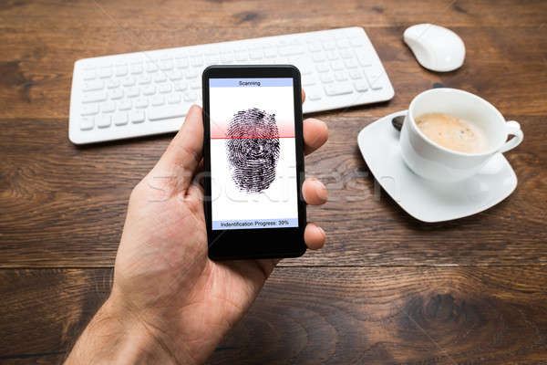 Person Hands Holding Mobile Phone With Fingerprint Application Stock photo © AndreyPopov