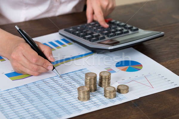 Businessperson With Coins Over Graph And Report Stock photo © AndreyPopov