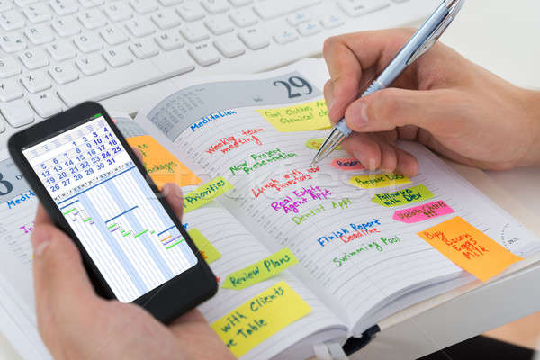 Person Hands With Mobile Phone And Diary Stock photo © AndreyPopov
