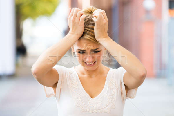 Stock photo: Woman Suffering From Headache Outdoors