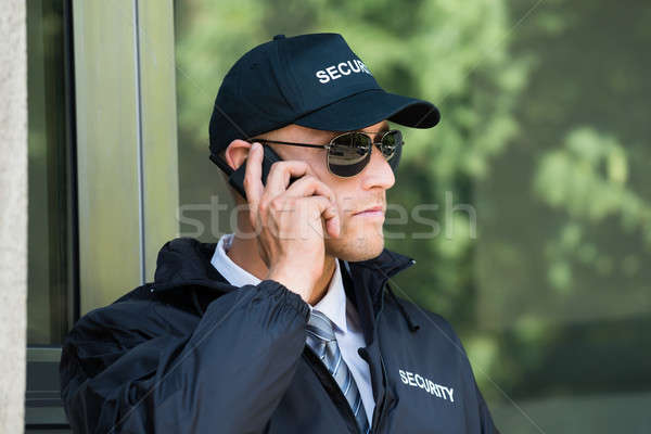 Stock photo: Young Security Guard Talking On Walkie-talkie