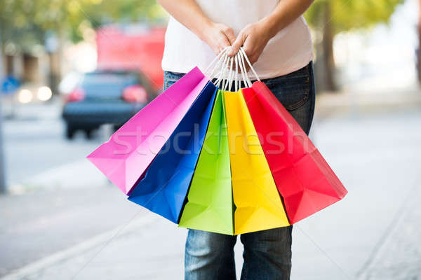 Midsection Of Woman Holding Colorful Shopping Bags Stock photo © AndreyPopov