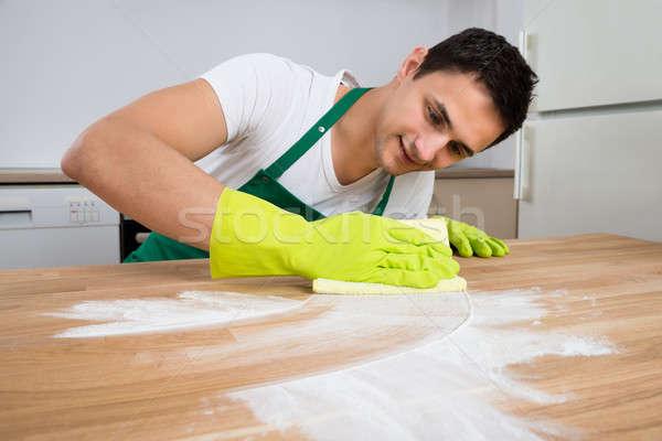 Czystsze czyszczenia pyłu drewniany stół uśmiechnięty mężczyzna Zdjęcia stock © AndreyPopov