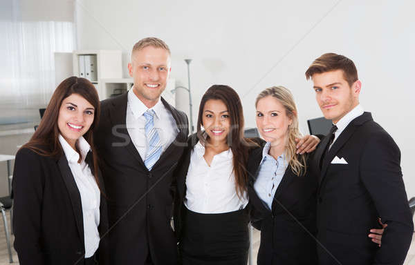 Professionals Standing Arms Around In Office Stock photo © AndreyPopov