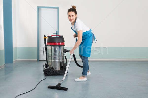 Fiatal női gondnok takarítás padló porszívó Stock fotó © AndreyPopov