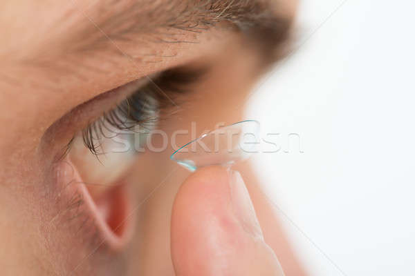 Man Putting Contact Lens In Eye Stock photo © AndreyPopov