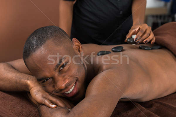 Man Getting Hot Stone Therapy Stock photo © AndreyPopov