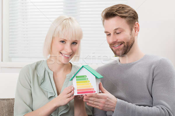 Couple Showing Energy Efficiency Rate On House Model Stock photo © AndreyPopov