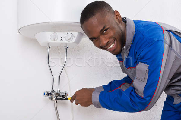 Worker Repairing Electric Boiler With Wrench Stock photo © AndreyPopov