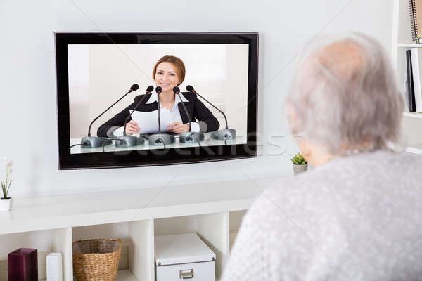 Grandmother Watching News On Television Stock photo © AndreyPopov
