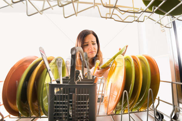 Woman Looking At Plate Near Dishwasher Stock photo © AndreyPopov
