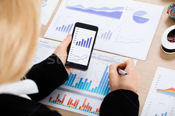Businesswoman Analyzing Graph Using Mobilephone Stock photo © AndreyPopov