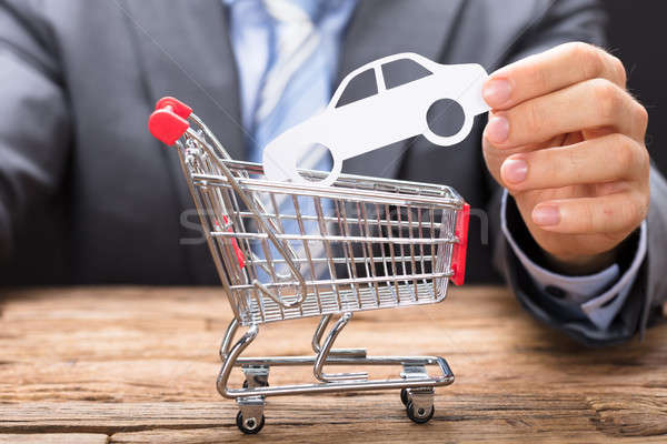 Businessman Holding Paper Car Over Shopping Cart Stock photo © AndreyPopov