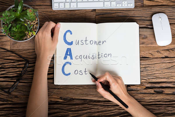 Businessperson Writing Customer Acquisition Cost Concept Stock photo © AndreyPopov