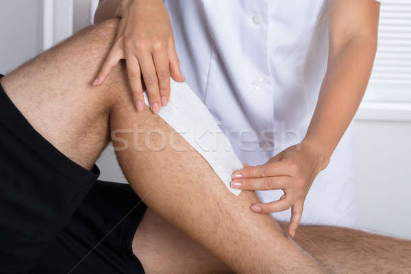 Therapist Waxing Man's Leg Stock photo © AndreyPopov