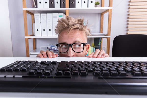 Funny empresario ocultación detrás escritorio Foto stock © AndreyPopov
