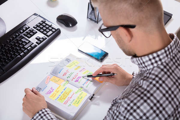 Businessperson With Mobile Phone Writing Schedule Stock photo © AndreyPopov