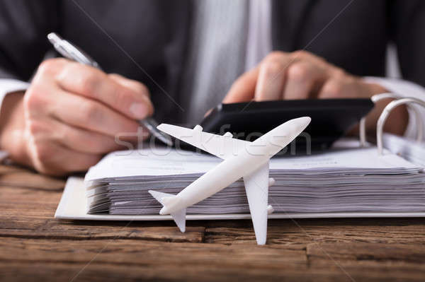White Aeroplane In Front Of Businessperson Calculating Invoice Stock photo © AndreyPopov
