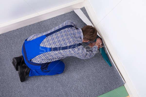 Worker Fitting Carpet On Floor Stock photo © AndreyPopov