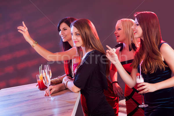Beautiful girls ordering drinks at the bar Stock photo © AndreyPopov