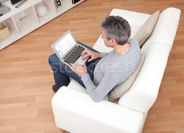 Senior man sitting in sofa and using laptop Stock photo © AndreyPopov