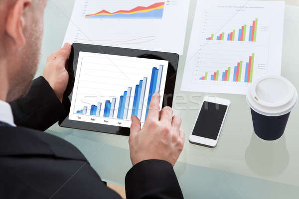 Businessman analyzing a graph on a tablet Stock photo © AndreyPopov