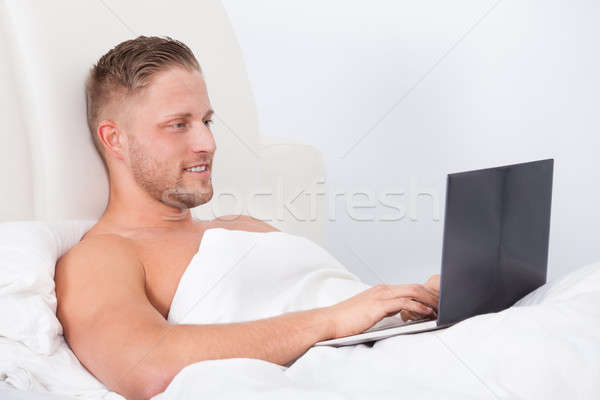 Man sitting up in bed against the pillows Stock photo © AndreyPopov