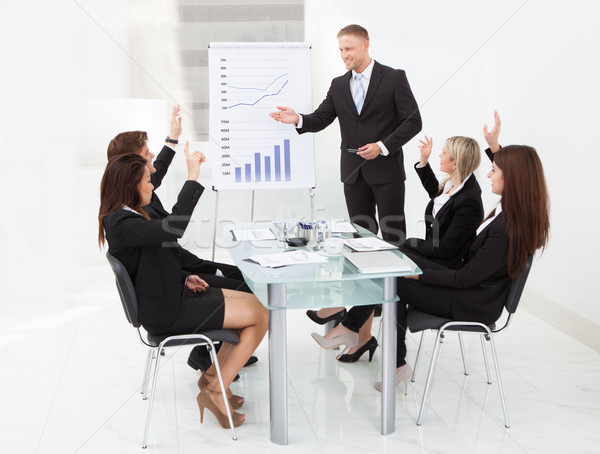 Businesspeople Answering Businessman In Meeting Stock photo © AndreyPopov