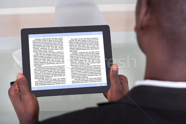 üzletember olvas ekönyv közelkép afrikai történet Stock fotó © AndreyPopov