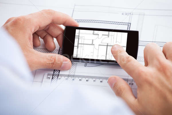 Architect Analyzing Blueprint On Mobilephone Stock photo © AndreyPopov