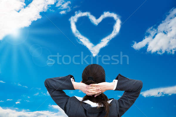 Businesswoman Looking At Heart Shaped Cloud In Sky Stock photo © AndreyPopov