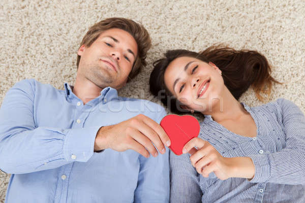 Couple Holding Heart While Lying On Rug Stock photo © AndreyPopov
