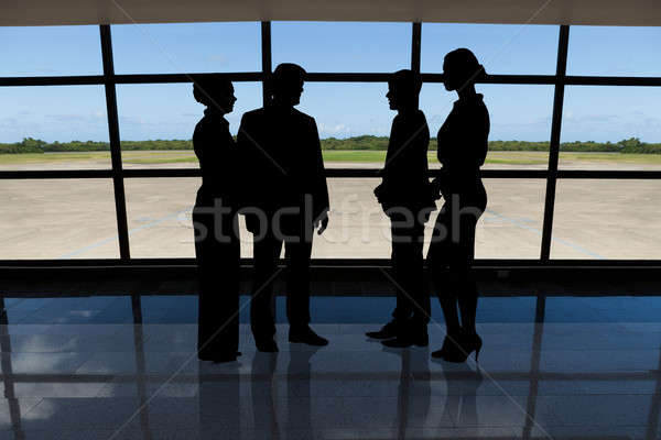 Businesspeople standing against airport window Stock photo © AndreyPopov