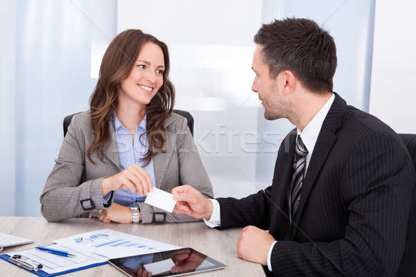 Businessman And Businesswoman Exchanging Visiting Card At Office Desk Stock photo © AndreyPopov