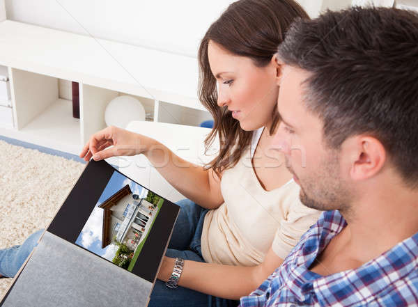 Couple Sitting On Couch Looking At Picture Of Real Estate Stock photo © AndreyPopov