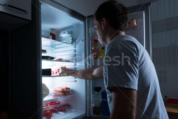 Man Taking Food From Fridge Stock photo © AndreyPopov
